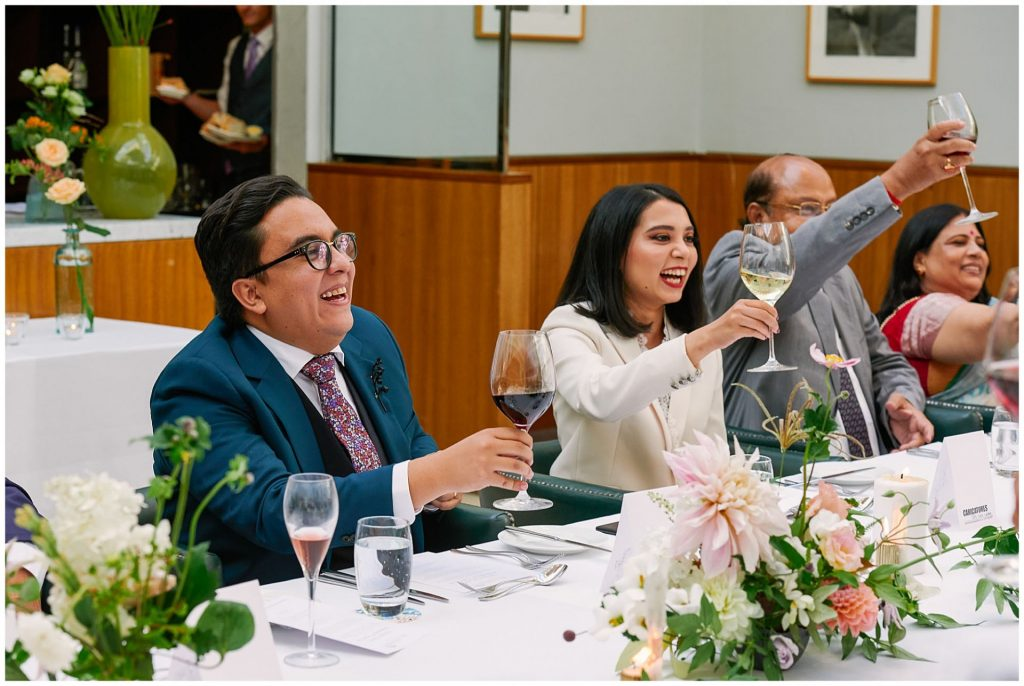brides and groom laughing whilst toasting with drinks during wedding speeches at The Bluebird in Chelsea, London