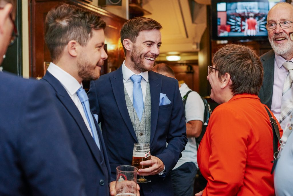 Groom laughing and drinking beer in a London pub with wedding guests