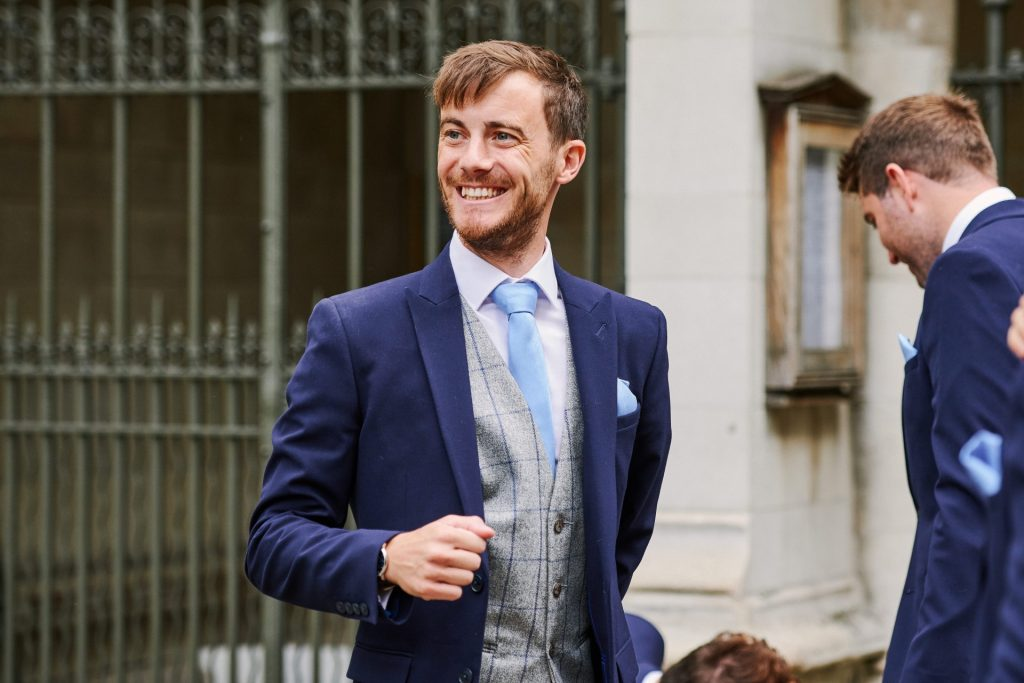 Groom smiling outside of St Margaret's Church in central London
