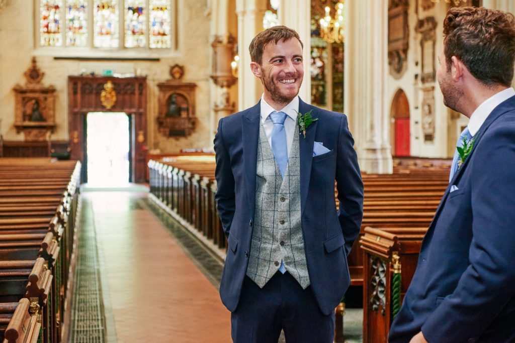Groom stood smiling inside St Margaret's Church in central London