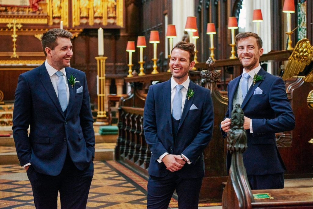Groom and ushers stood smiling inside St Margaret's Church in central London