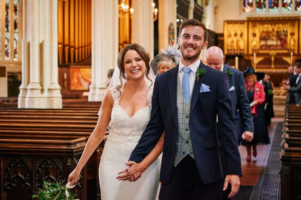 Bride and groom smiling together in St Margret's Church in London