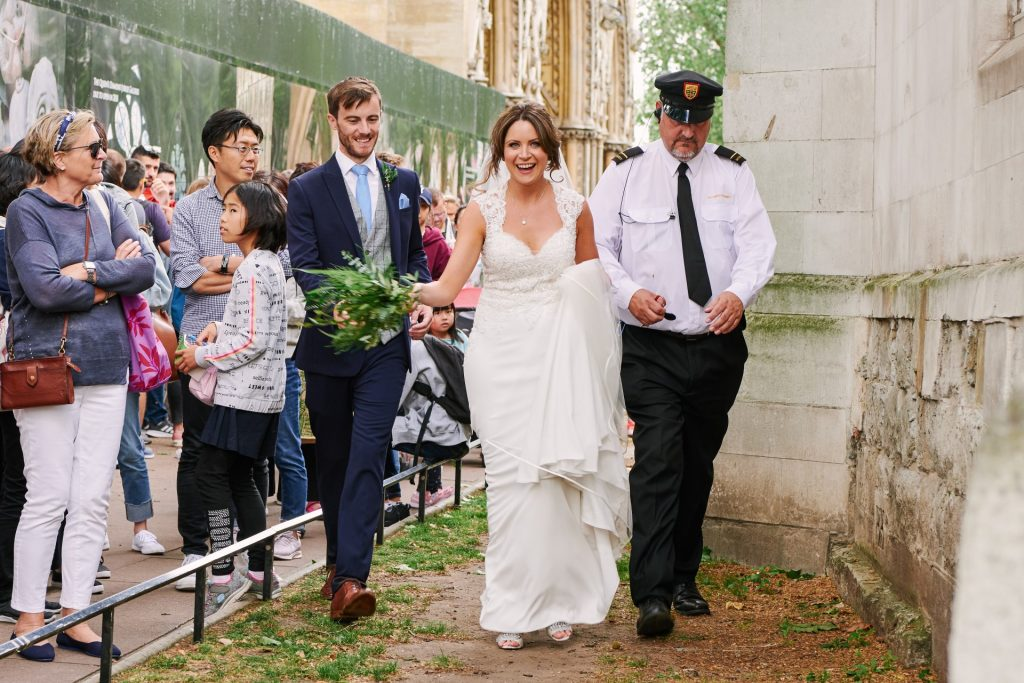 Bride and groom being escorted by a police man in central London.