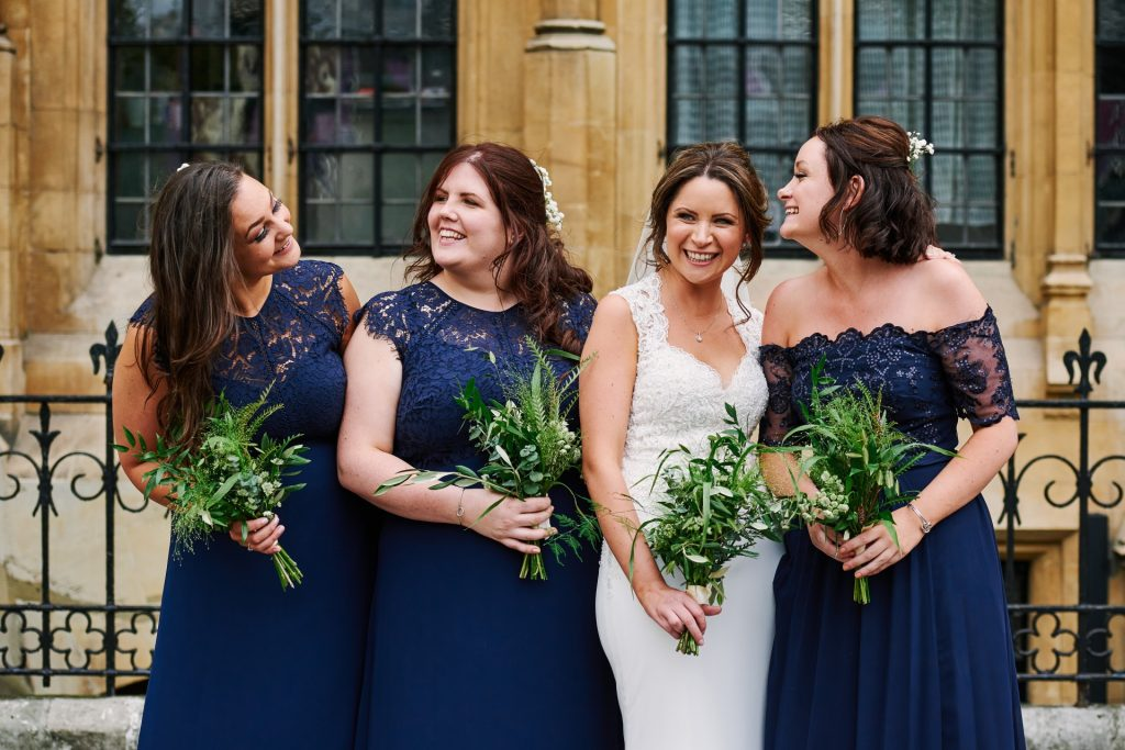 Bride laughing with her bridesmaids  outside of an old London building