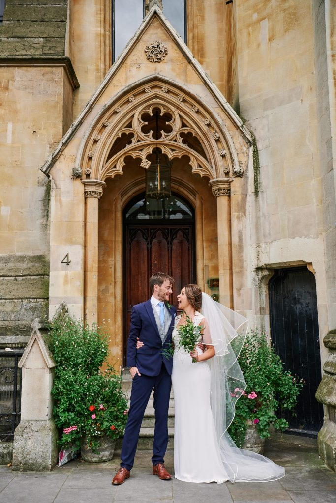 Bride and groom smiling together outside of an old doorway in London