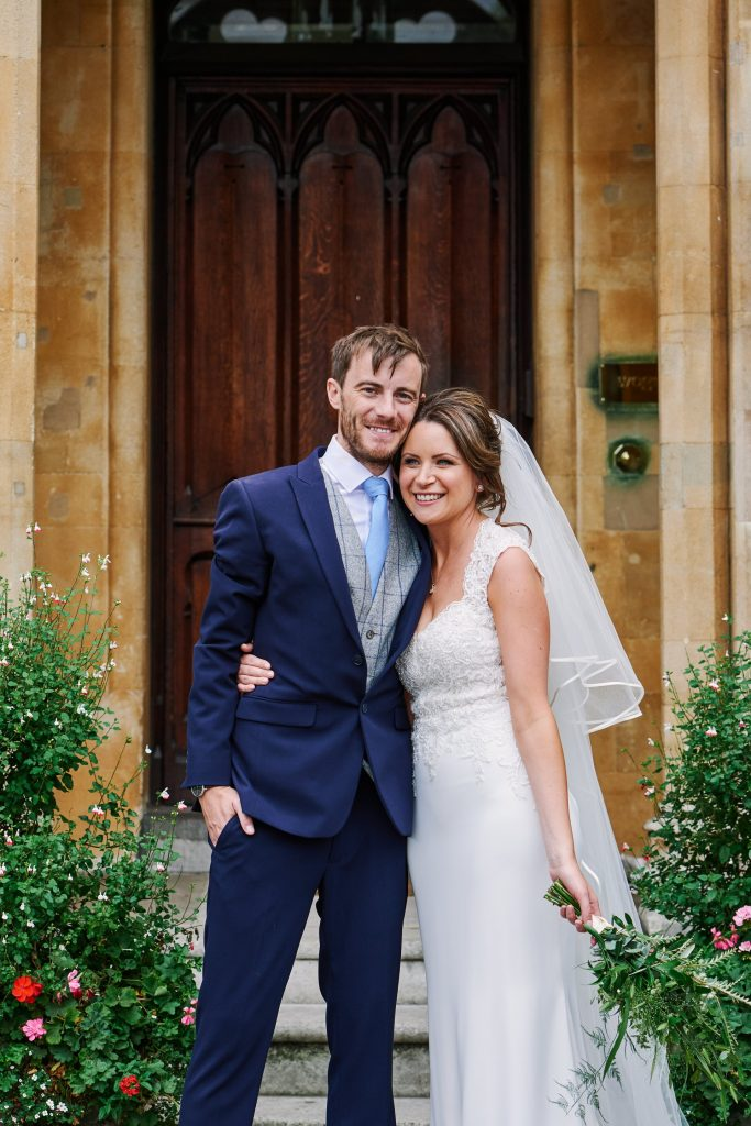 Bride and groom smiling together outside of Westminster church in London