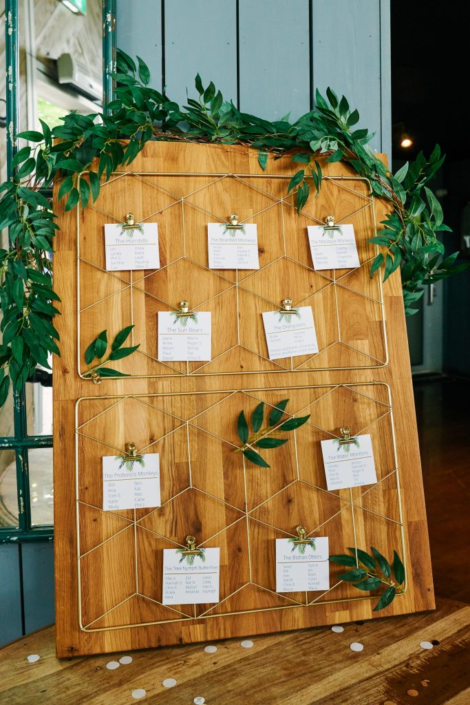 Wedding table plan on plank of wood with pegged paper on it.