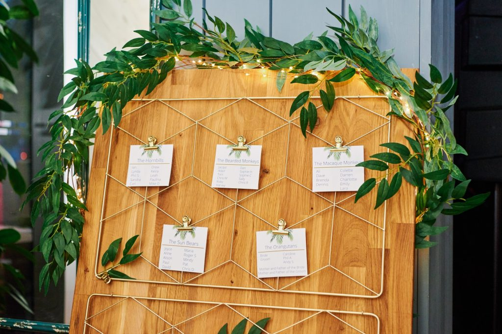 wedding table plan on plank of wood with paper clipped to geometric frame
