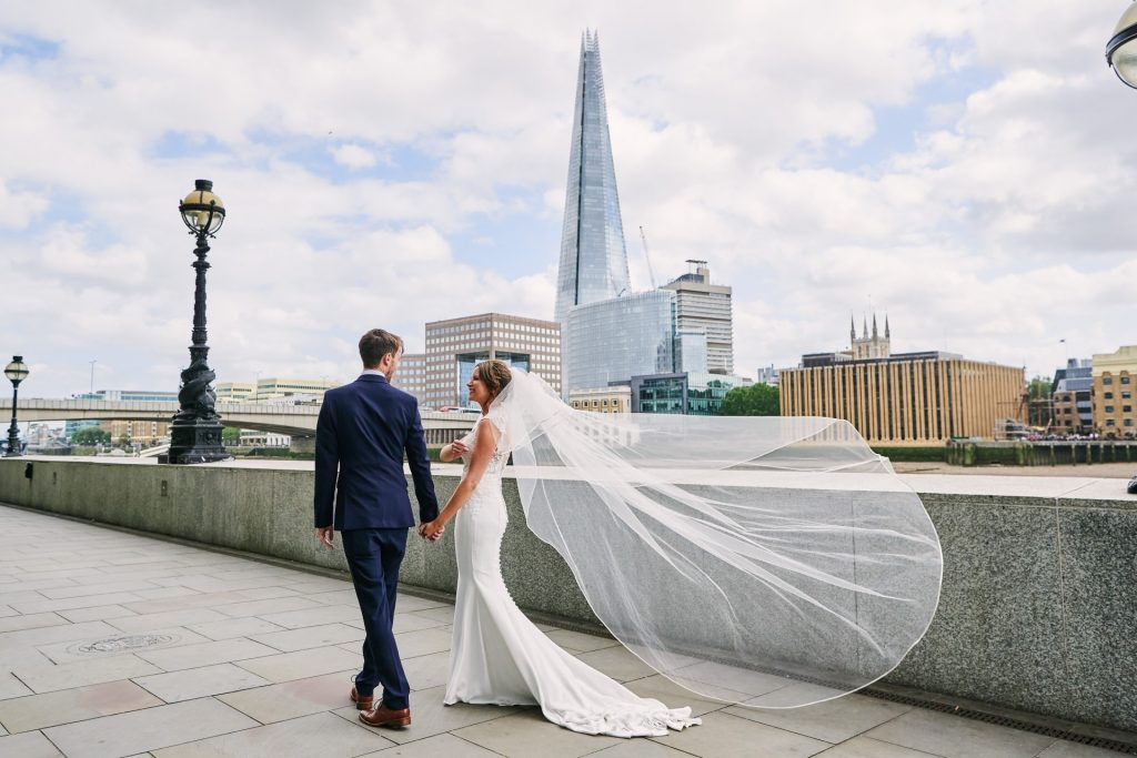 bride and groom walking along the riverside whilst veil blows in the wind