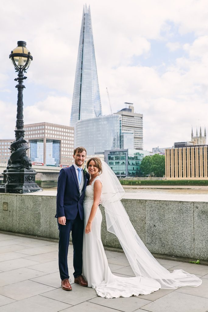 Bride and groom stood along the riverside with a view of the Shard behind them.