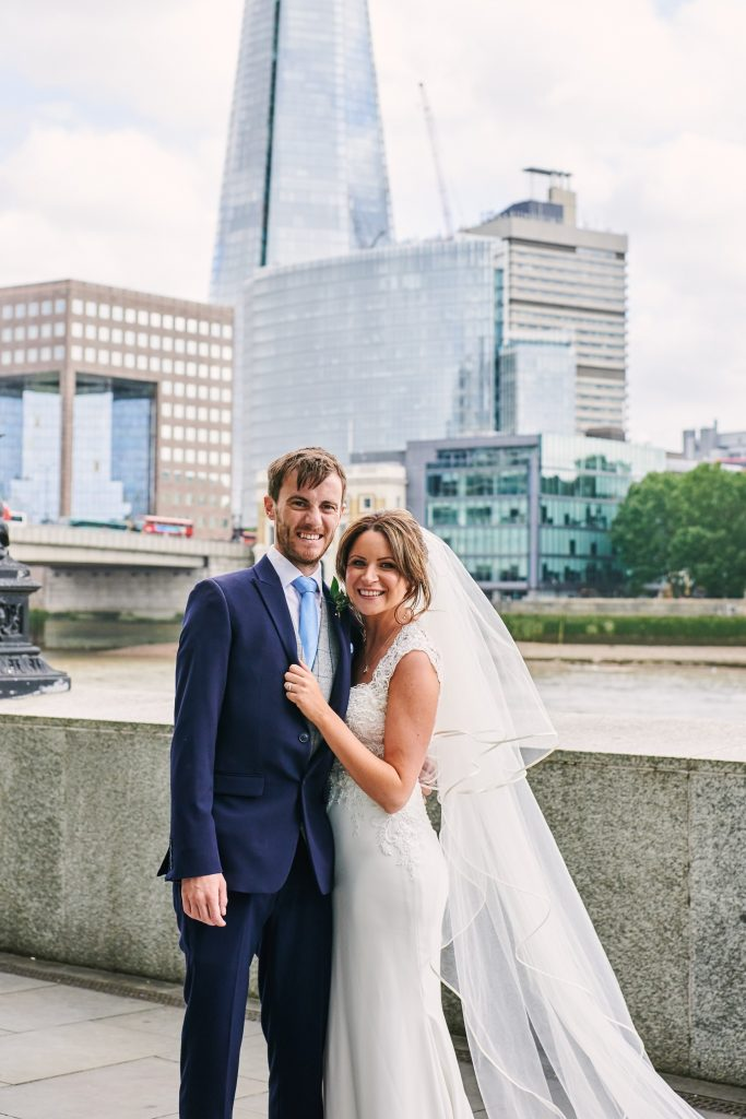 Wedding couple stood in front of The Shard outside of the riverside venue The Oyster Shed