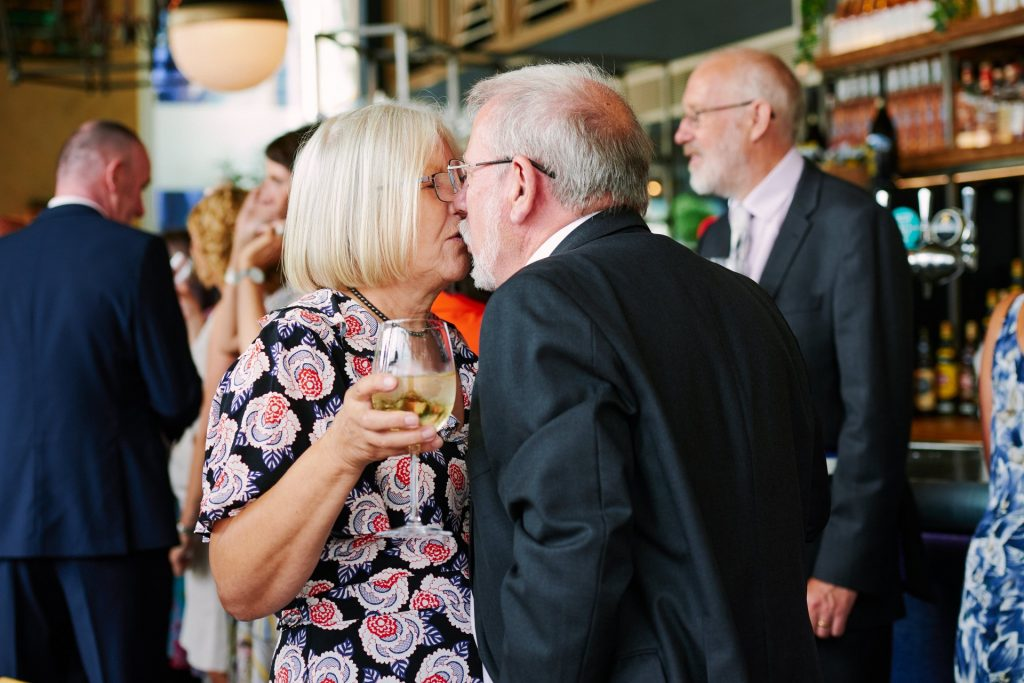 Old couple kissing whilst at a wedding reception at The Oyster Shed