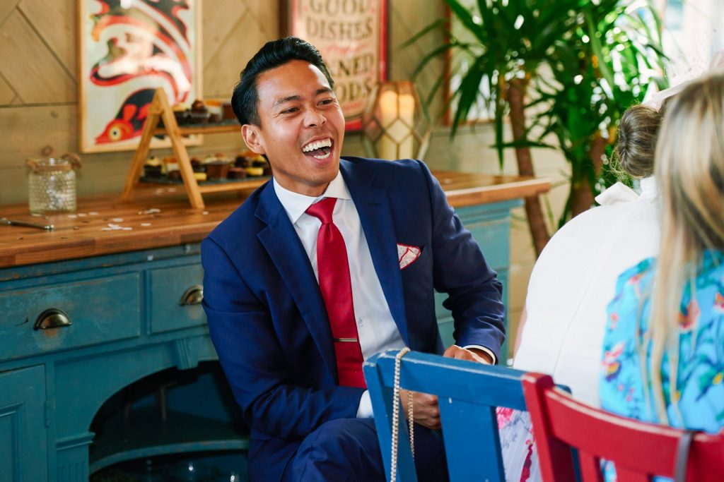 male wedding guest laughing whilst sat down for dinner at the Oyster Shed