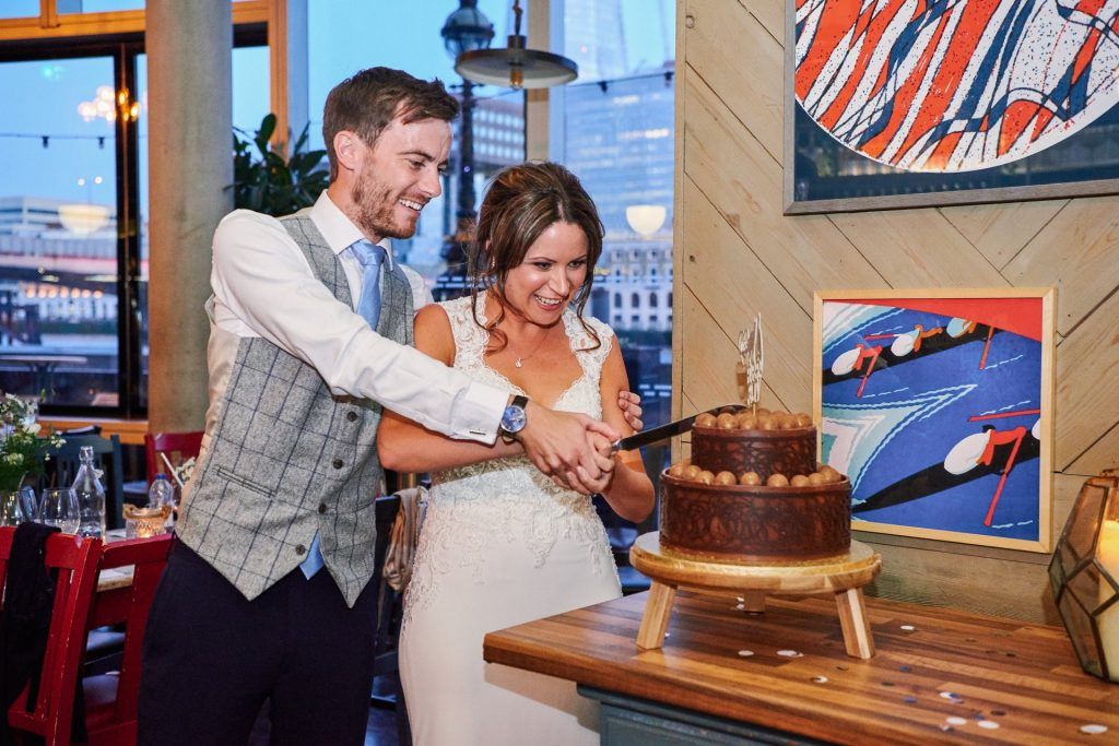 Bride & Groom cutting chocolate wedding cake at The Oyster Shed in London
