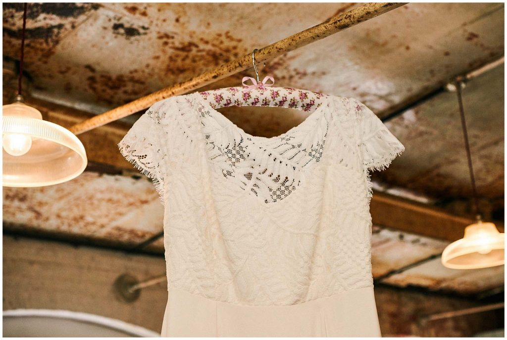 Brides wedding dress hung up against a rustic metal background at The West Mill