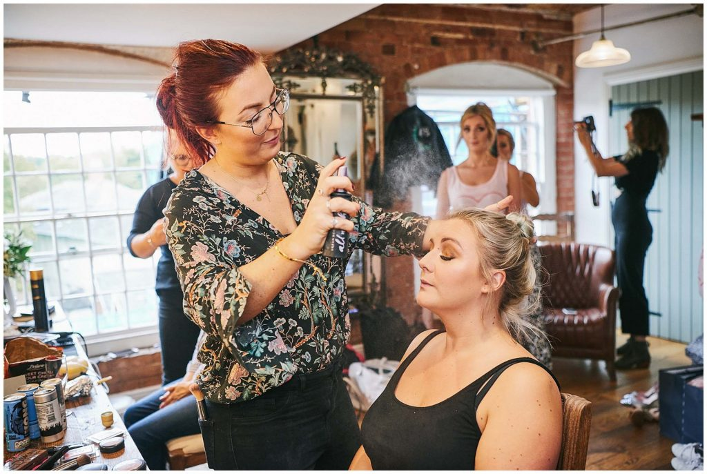 bride having mist sprayed in her face during bridal prep in rustic room