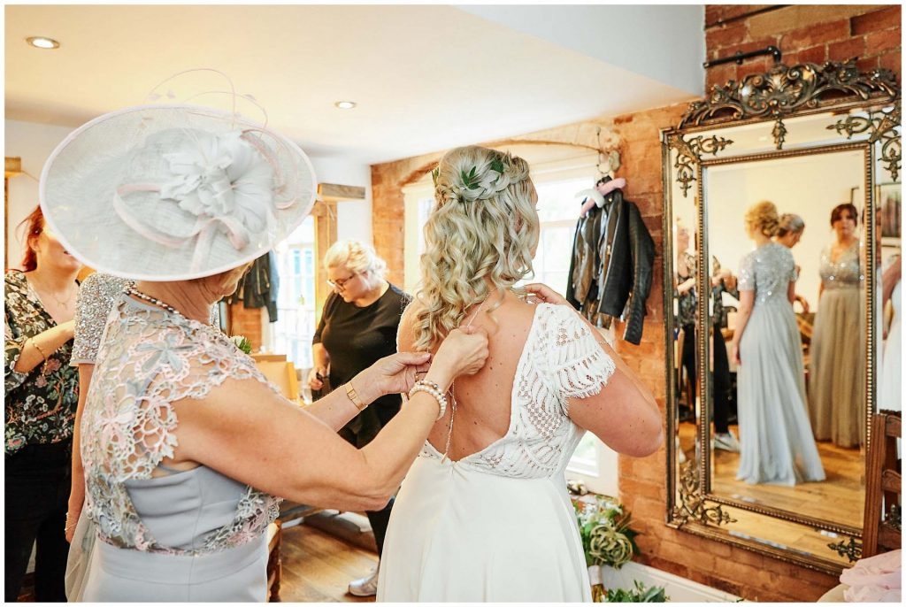 Brides mum helping bride put on her jewellery in the dressing room at The West Mill Wedding Venue