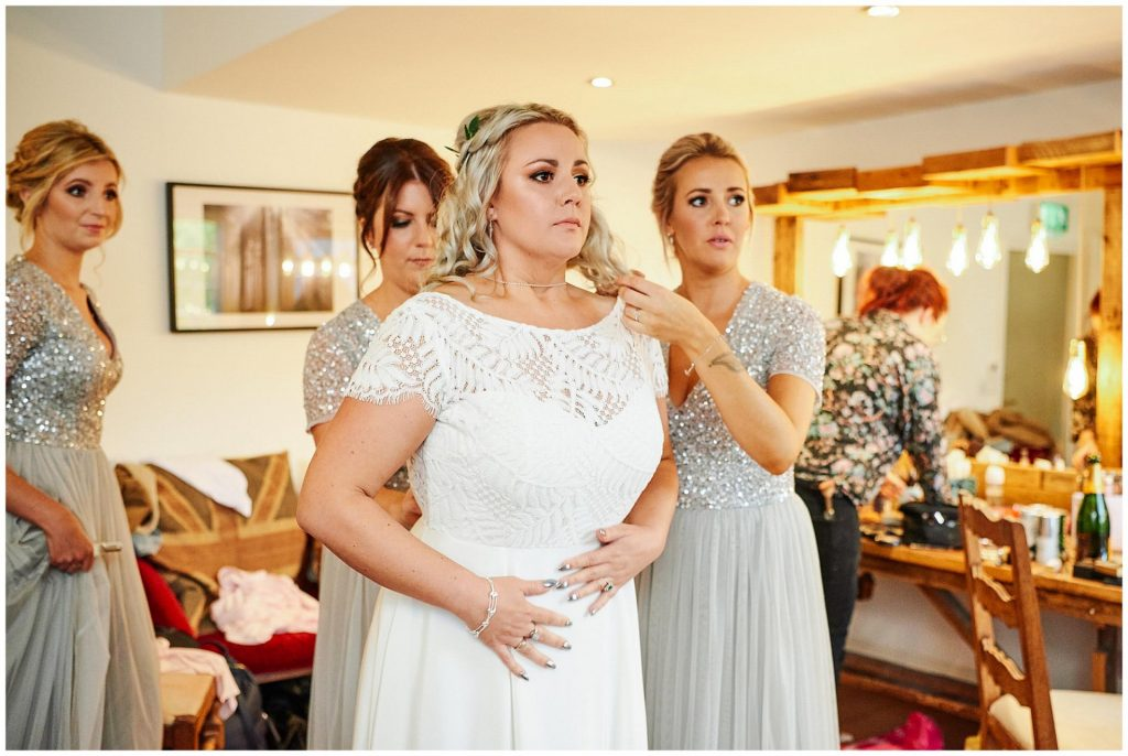Bride looking nervous during bridal prep in the dressing room at The West Mill Wedding Venue in Derby