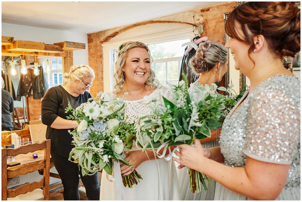Bride laughing and holding flowers  at The West Mill Wedding Venue in Derby