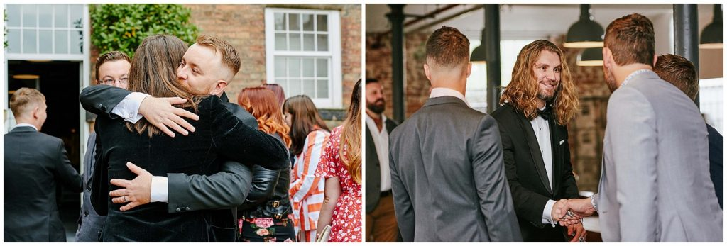 Guests hugging and greeting each other at the industrial looking West Mill Wedding Venue in Derby