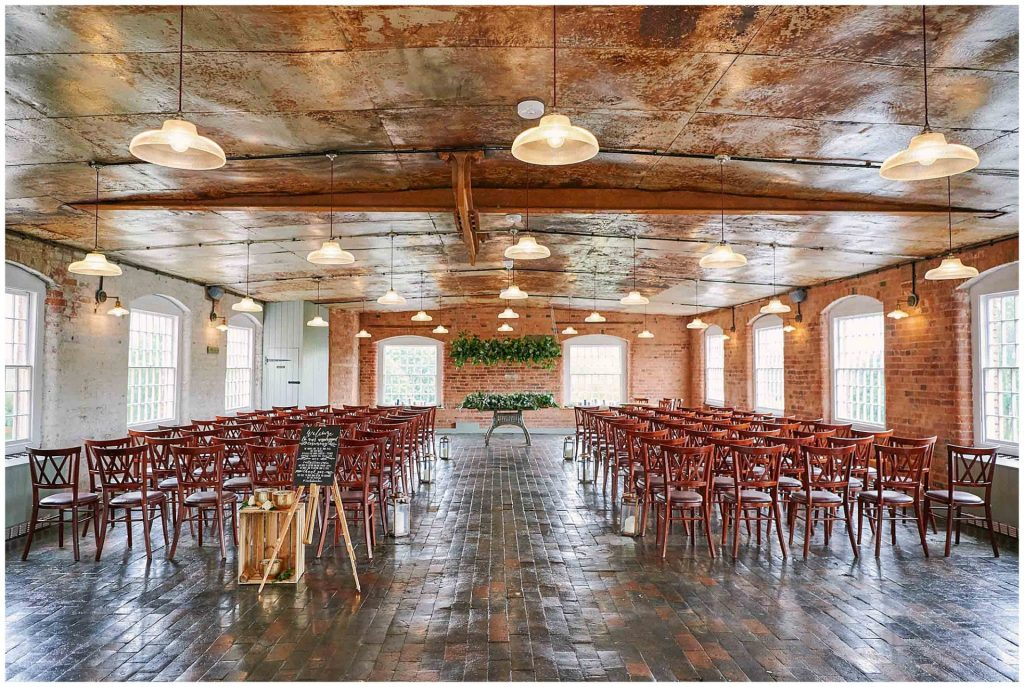 Empty ceremony room with a rustic brick wall and industrial metal ceiling at the West Mill Wedding Venue in Derby