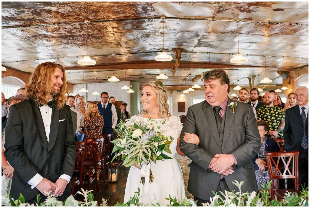 Bride and her father smiling at the groom during a wedding ceremony at the West Mill Venue in Derby