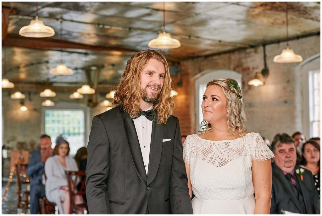 Bride and groom smiling at each other during their wedding ceremony at the industrial West Mill Venue in Derby