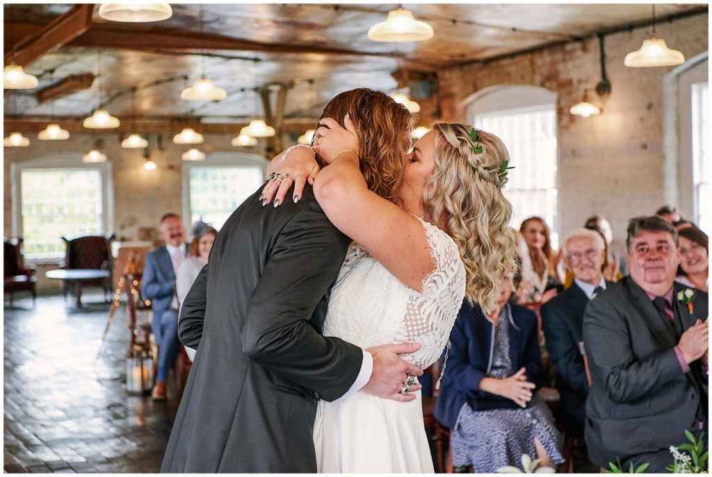 Bride and grooms first kiss during their wedding ceremony at the industrial looking West Mill Venue in Derby
