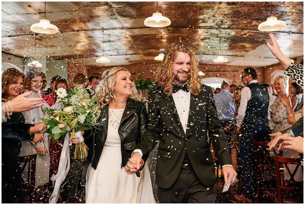 Rock n Roll wedding couple walking down isle whilst confetti is thrown over them at The West Mill in Derbyshire