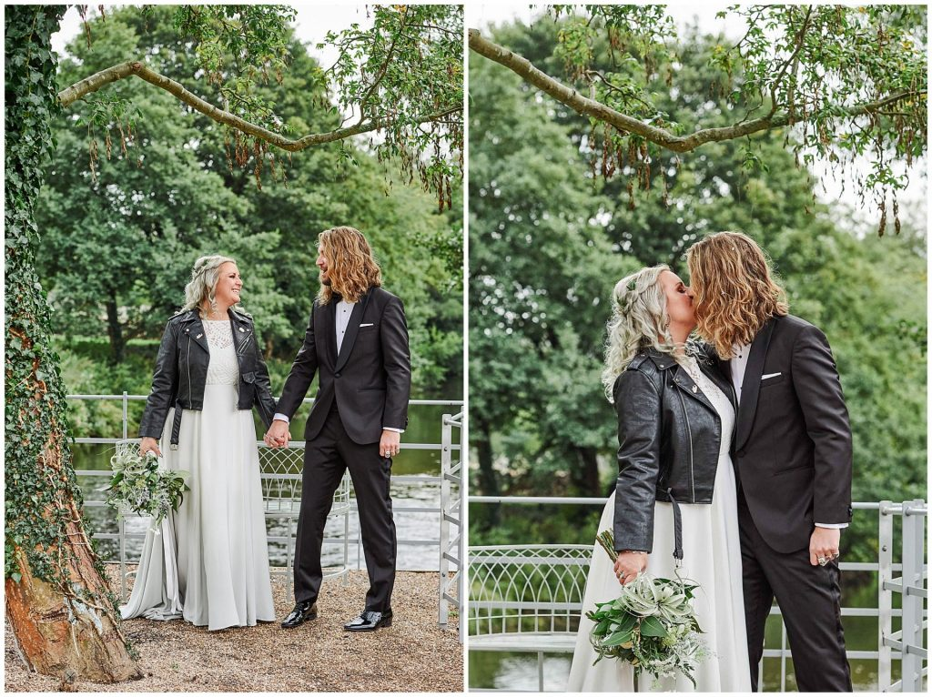 Alternative Bride and groom holding hands and kissing in front of green trees