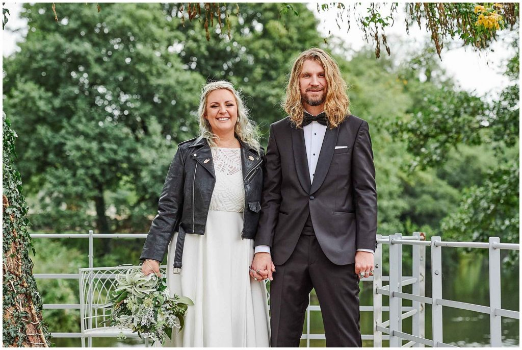 Rock and Roll style Bride and groom holding hands in front of green trees at the West Mill Wedding Venue in Derby