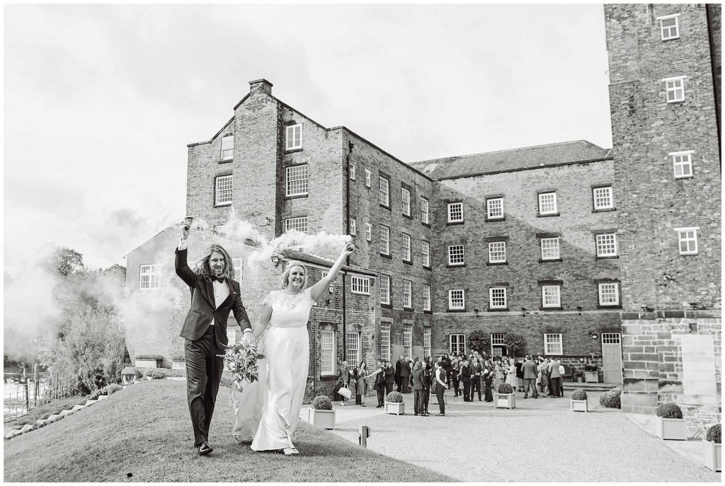 Bride and groom holding smoke bombs with the industrial West Mill Wedding Venue in the background.