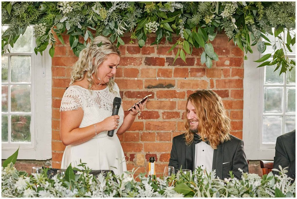 Bride crying whilst reading speech to the groom in front of a brick wall and green floral decorations at the West Mill in Derby.