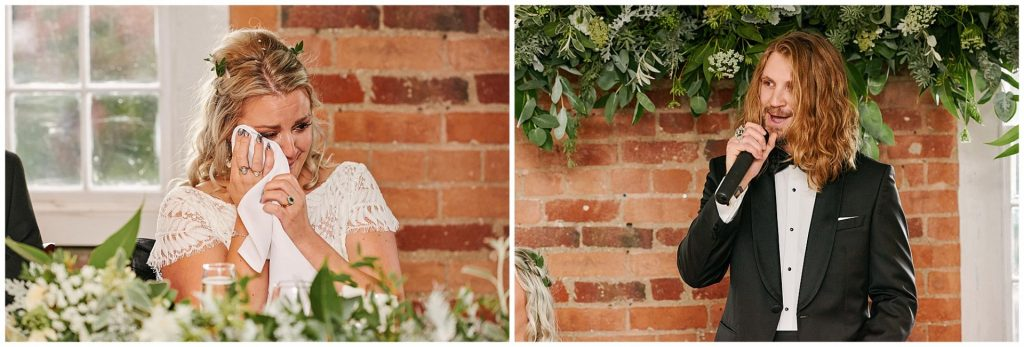 Bride crying whilst groom is reading speech in front of a brick wall and green floral decorations at the West Mill in Derby.