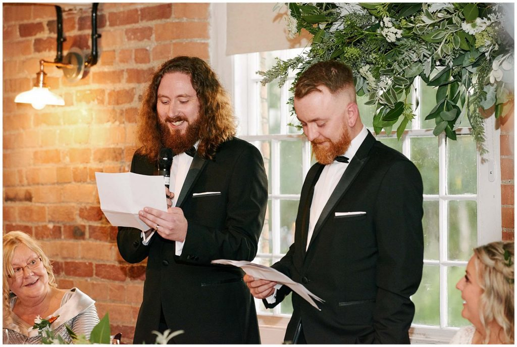 Two best men laughing whilst reading speech in front of a window and brick wall at the West Mill in Derby.