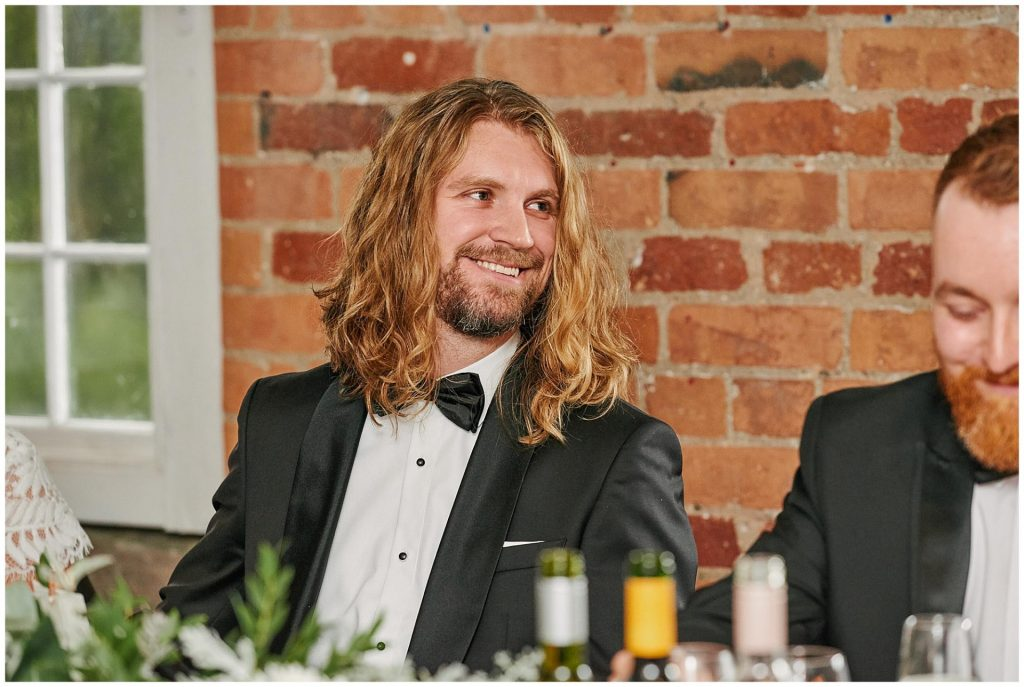 Groom in a black suit sat down laughing in front of a brick wall at the West Mill in Derby.