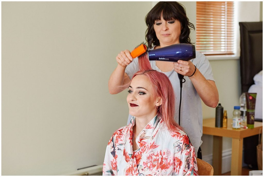 Bride with pink hair having it styled whilst wearing a floral dressing gown.