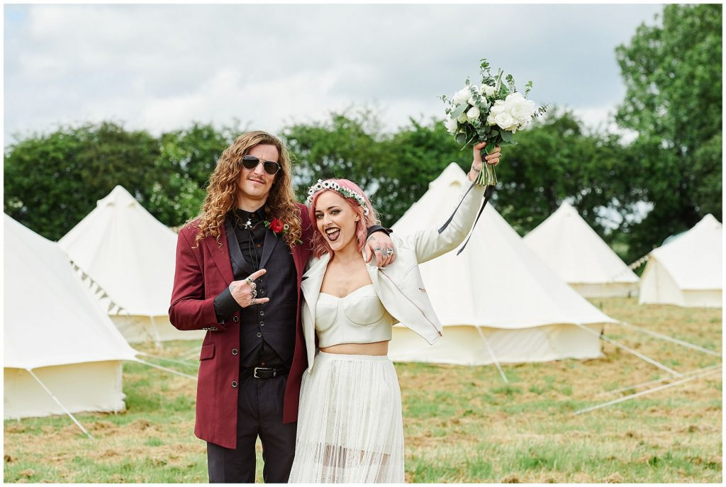 Rock n roll Bride and Groom celebrating in front of festival tipis.