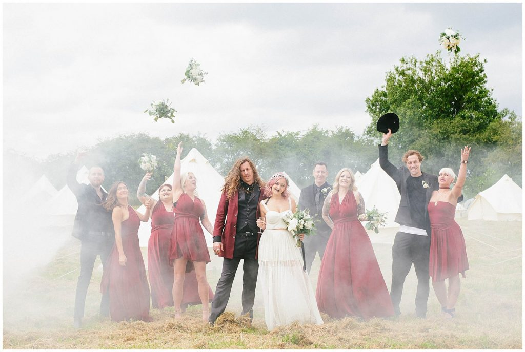 Bridal party stood in front of tipis and smoke bombs during a festival style wedding.