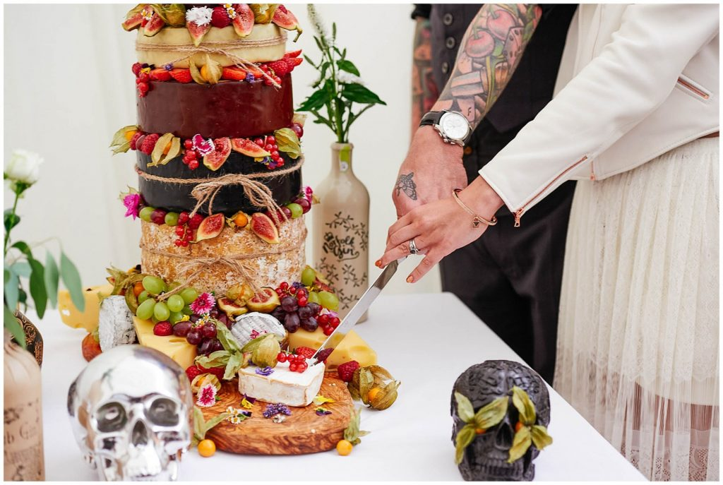 Bride and grooms hands cutting cheese wedding cake with rock n roll skulls