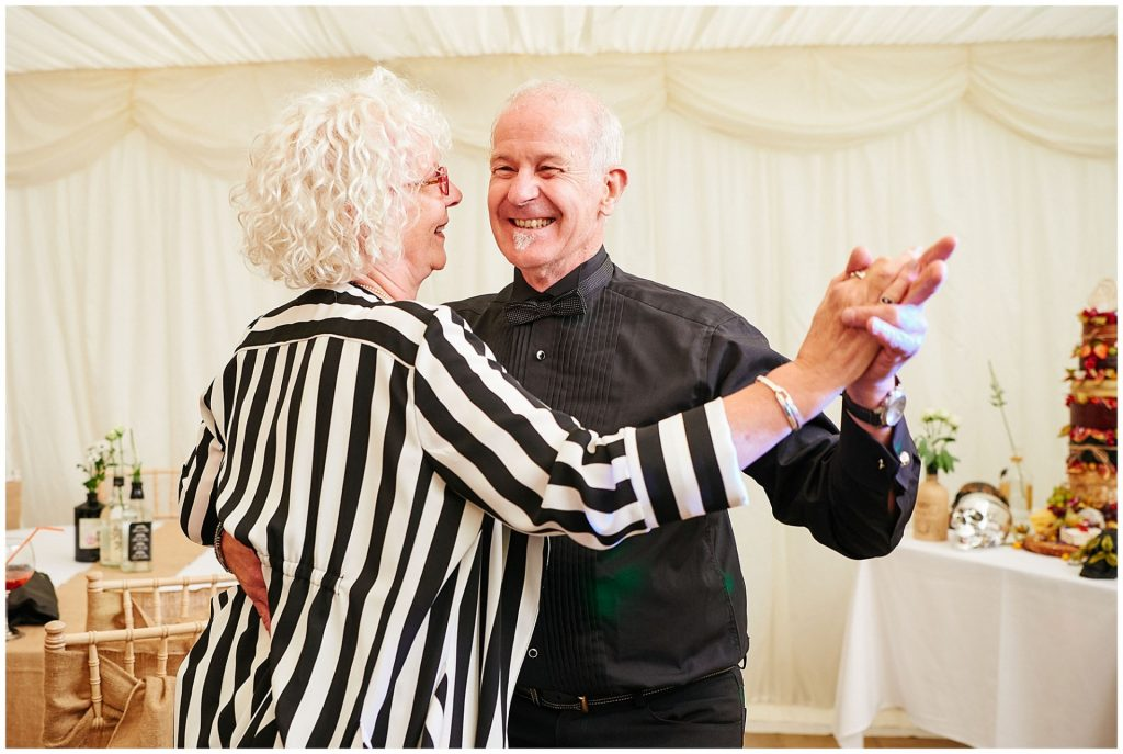 Old couple dancing together in a wedding marquee at The Peasantry Brewery