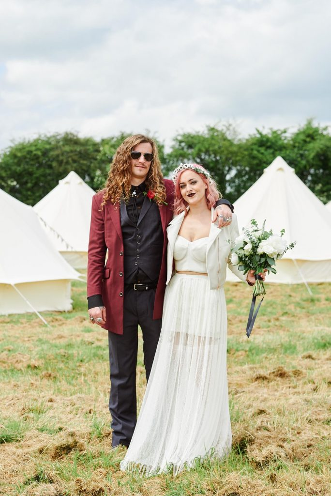 Alternative Bride and groom stood in front of festival tipis at The Peasantry Brewery