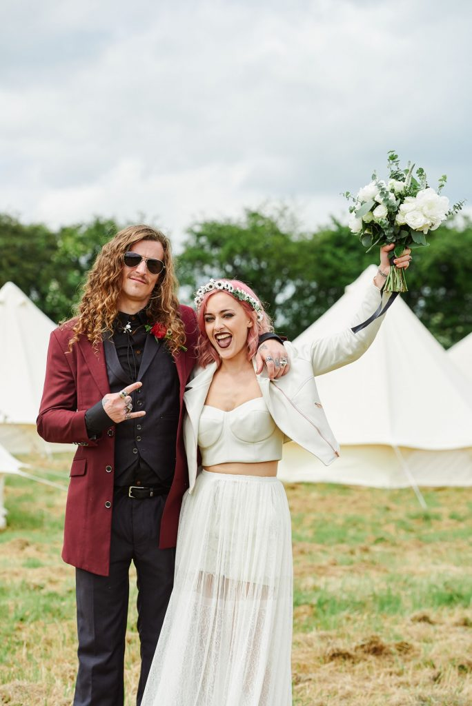Rock n Roll style Bride and groom stood in front of festival tipis at The Peasantry Brewery