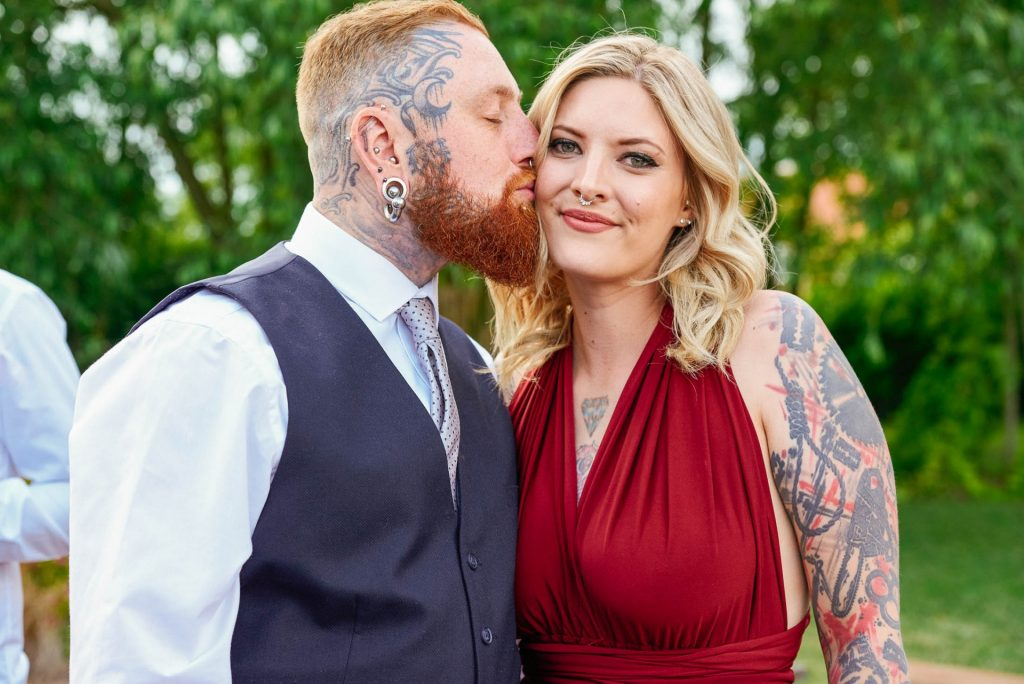 Tattooed wedding couple kissing whilst stood outside at the The Peasantry Brewery