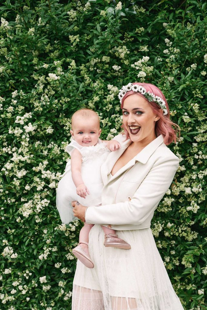 Bride with pink hair wearing a white leather jacket and holding a baby