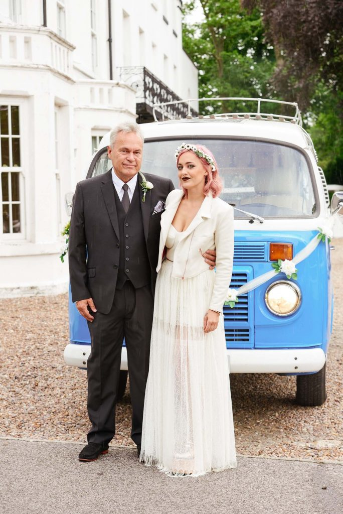 Bride with pink hair stood with her dad in front of festival style VW Camper van