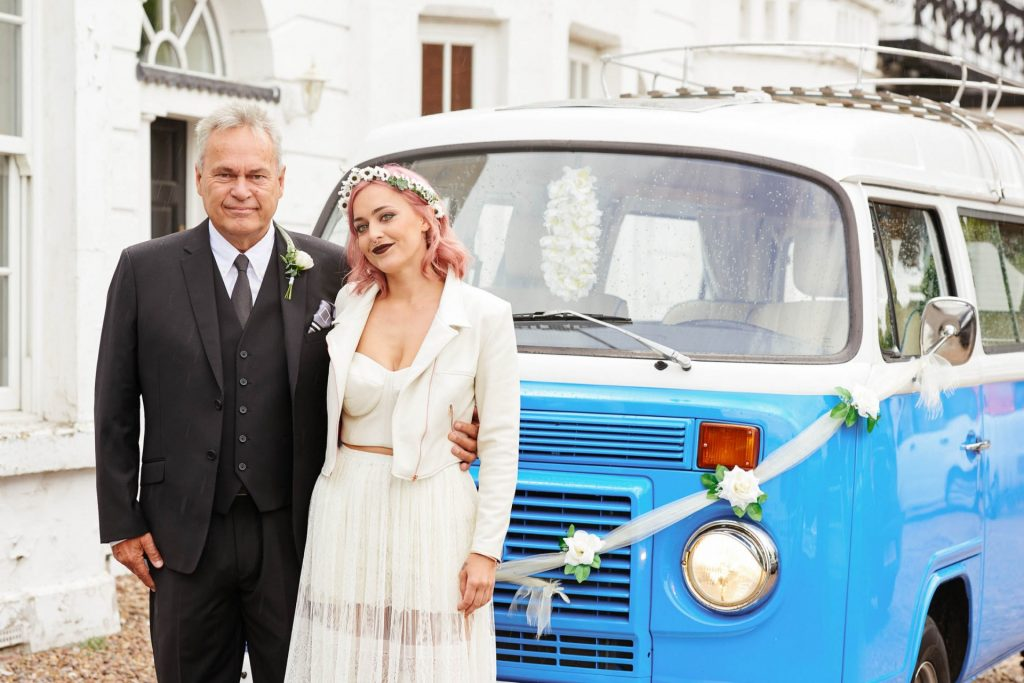 Bride with pink hair stood with her dad in front of festival style VW Camper van on wedding day