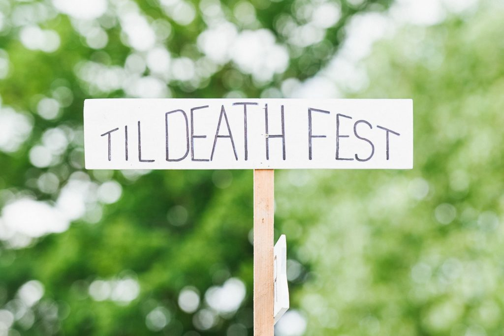 Festival style sign saying 'Till Death Fest' in front of green background