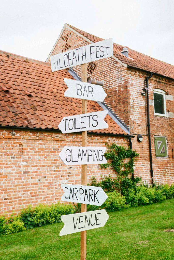 Festival style sign pointing out directions at the The Pheasantry Brewery wedding venue