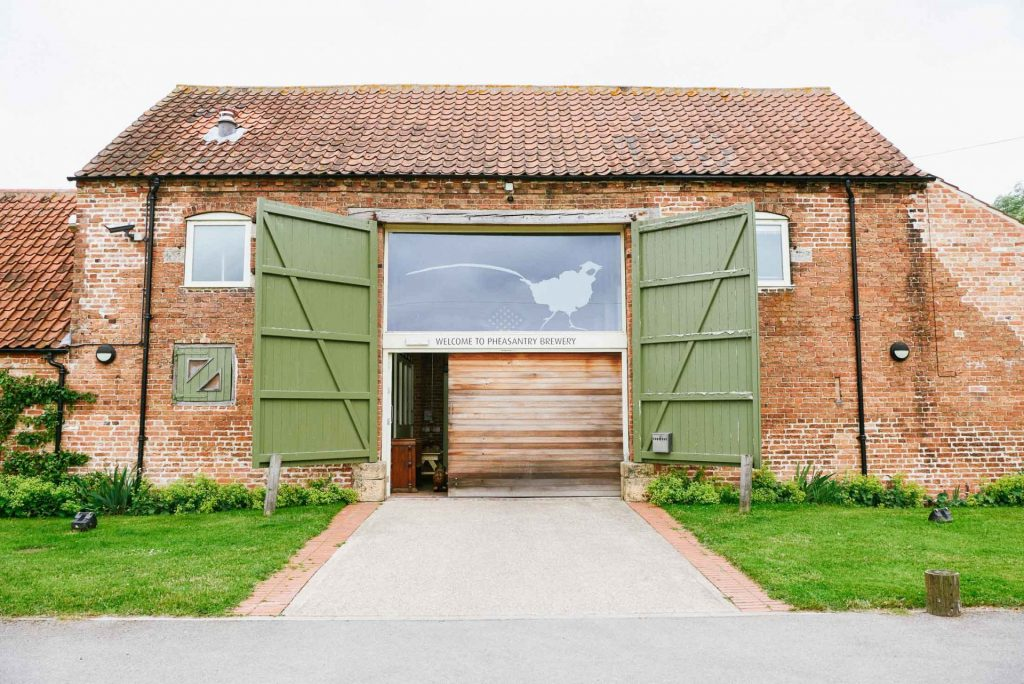 Exterior shot of the The Pheasantry Brewery wedding venue with it's barn doors open.